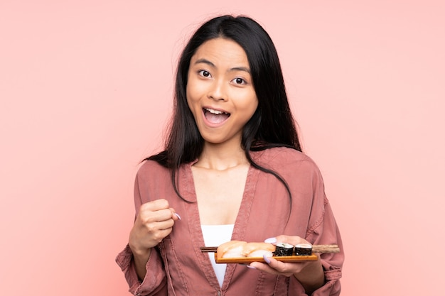 Adolescent fille mangeant des sushis isolé sur rose célébrant une victoire