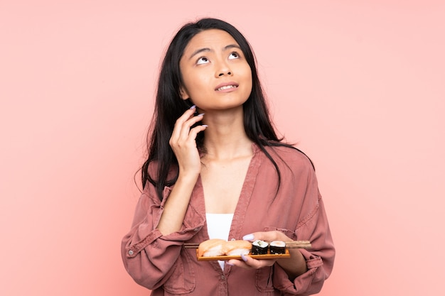 Adolescent fille mangeant des sushis isolé sur rose en pensant à une idée