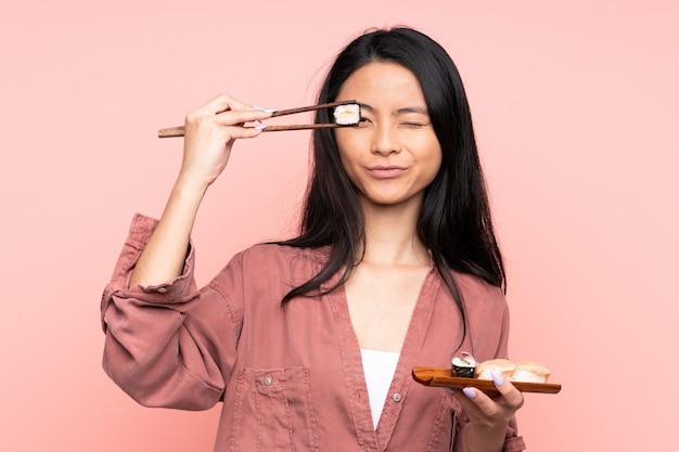 Adolescent fille mangeant des sushis isolé sur rose