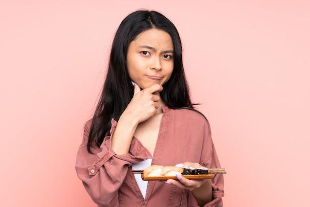 Adolescent fille manger des sushis isolé sur rose rire