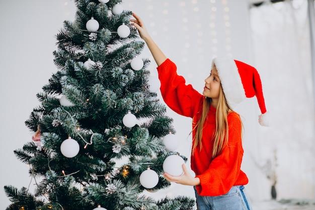 Adolescent fille mignonne en bonnet de noel rouge par arbre de noël