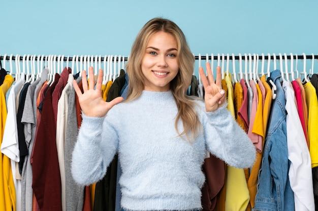 Adolescent fille russe acheter des vêtements isolés sur bleu comptant huit avec les doigts