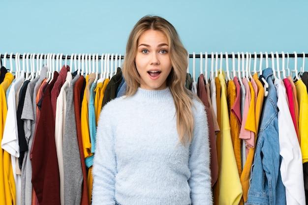 Adolescent fille russe acheter des vêtements isolés sur fond bleu avec une expression faciale surprise