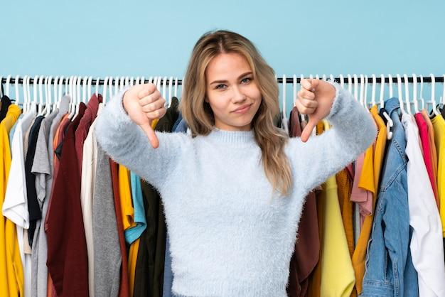 Adolescent fille russe acheter des vêtements sur le mur bleu montrant le pouce vers le bas