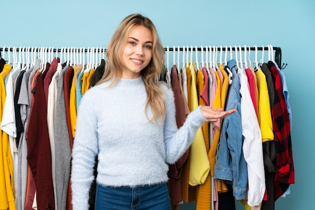Adolescent fille russe acheter des vêtements sur le mur bleu présentant une idée tout en regardant vers