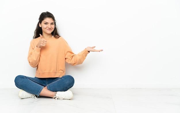 Adolescent fille russe assise sur le sol tenant copyspace imaginaire sur la paume pour insérer une annonce et avec les pouces vers le haut