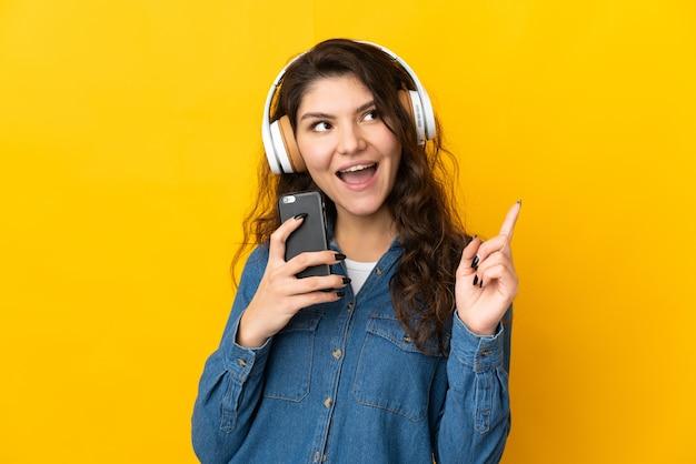 Adolescent fille russe isolée écouter de la musique avec un mobile et chanter