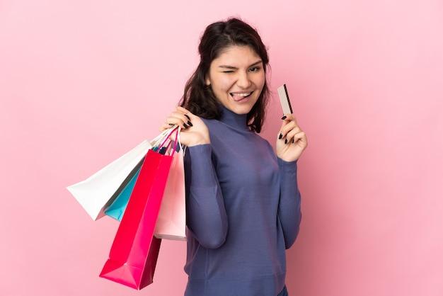 Adolescent fille russe isolée sur mur rose tenant des sacs et une carte de crédit