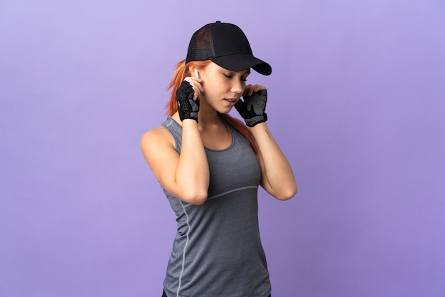 Adolescent fille russe isolée sur la musique d'écoute de mur violet