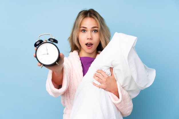 Adolescent fille russe en pyjama isolé sur bleu