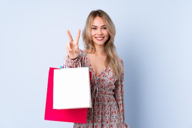 Adolescent fille russe avec sac à provisions isolé sur mur bleu souriant et montrant le signe de la victoire