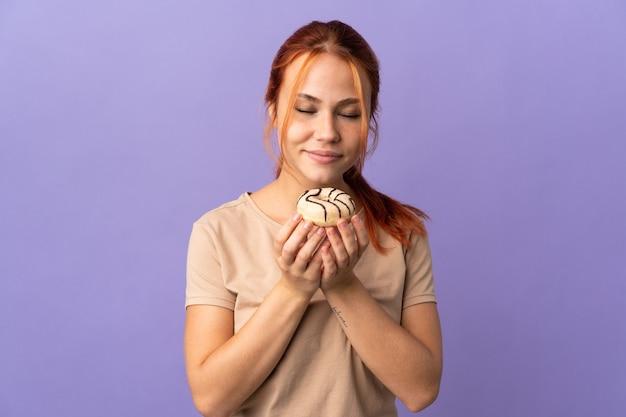 Adolescent fille russe sur violet tenant un beignet