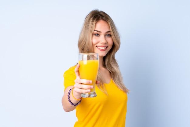 Adolescent fille tenant un jus d'orange isolé sur mur bleu avec une expression heureuse