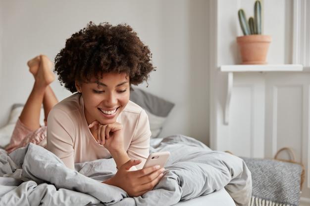 Adolescent gai à la peau sombre avec des cheveux afro, vêtu de vêtements de nuit, utilise un téléphone mobile