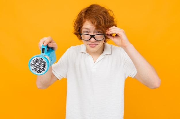 Adolescent garçon dans des verres et un t-shirt blanc loucher tout en tenant une lampe de poche à la main sur un fond jaune