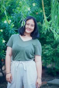 Adolescent grassouillet à pleines dents souriant visage dans un parc verdoyant