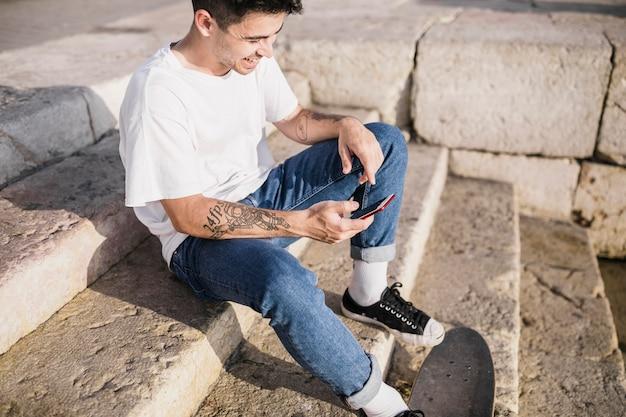 Adolescent heureux assis sur l'escalier avec skateboard et téléphone mobile