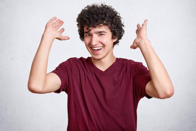 Adolescent heureux aux cheveux bouclés, vêtu d'un t-shirt décontracté