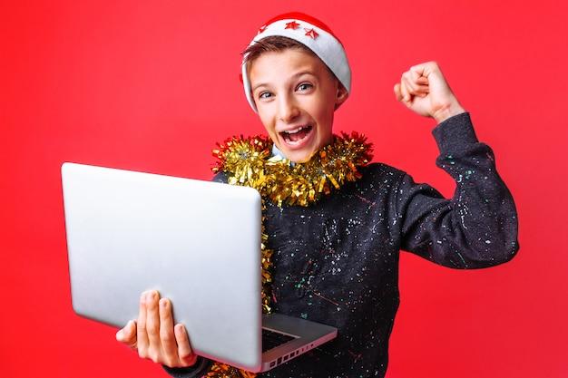 Adolescent heureux en bonnet de noel et avec des guirlandes sur son cou et tenant un ordinateur portable