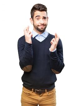 Adolescent heureux gardant ses doigts croisés