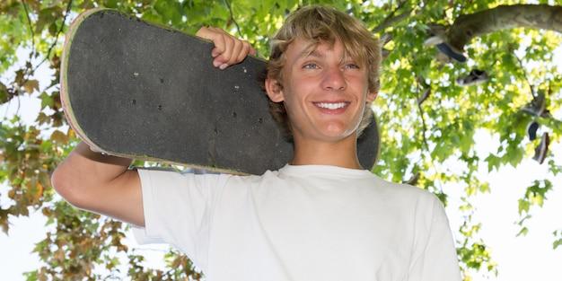 Adolescent heureux avec une planche à roulettes dans sa main et ses épaules