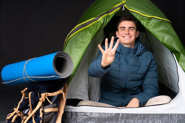 Adolescent homme caucasien à l'intérieur d'une tente de camping vert isolé sur fond noir heureux et en comptant quatre avec les doigts