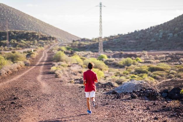 Adolescent ou homme courant seul dans les montagnes - mode de vie sportif - ondes positives