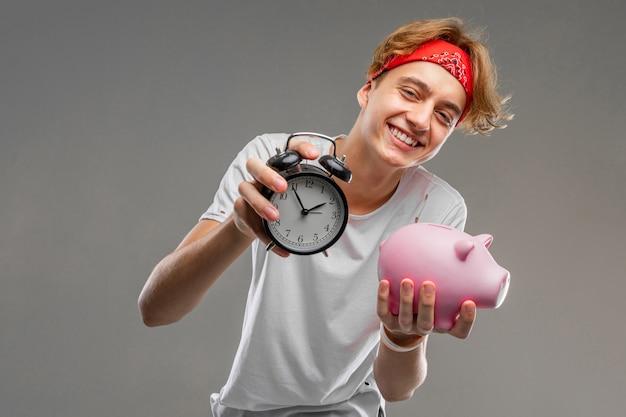 Adolescent avec horloge et tirelire, portrait demi-longueur d'un jeune homme dans un t-shirt léger