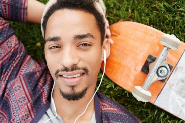 Adolescent insouciant reposant avec moustache et barbe à la mode se trouve à la pelouse verte près de sa planche à roulettes,