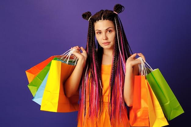 Adolescent jeune femme caucasienne tenant une pile de sacs colorés contre violet