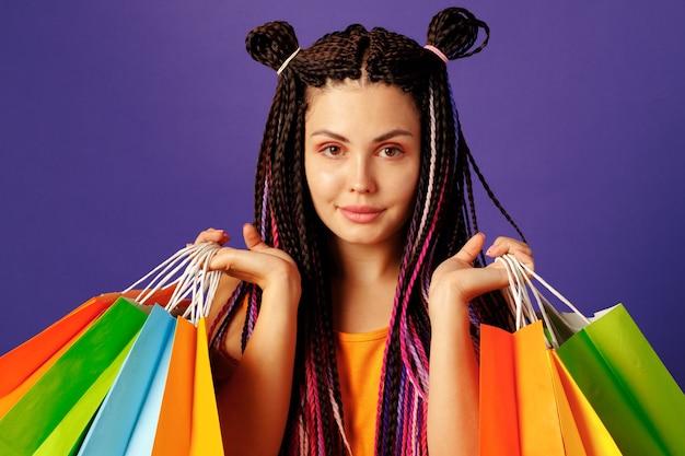 Adolescent jeune femme caucasienne tenant une pile de sacs colorés sur violet