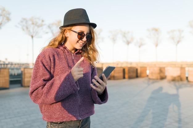 Adolescent, jeune fille, dans chapeau, et, lunettes, regarder, téléphone portable