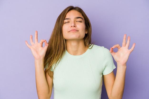 Adolescent jeune fille maigre caucasienne sur mur violet se détend après une dure journée de travail, elle effectue du yoga.