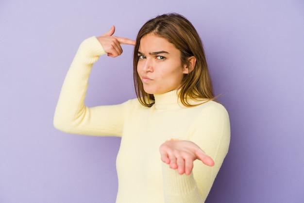 Adolescent jeune fille maigre caucasienne sur violet tenant et montrant un produit à portée de main.