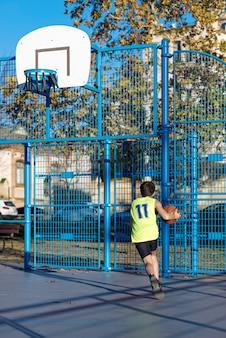 Adolescent jouant au basket-ball sur un terrain extérieur