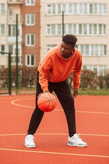 Adolescent jouant au basket en plein air