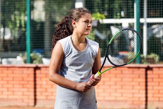 Adolescent, joueur tennis, formation, cour, fille, raquette, balle, cheveux longs, soleil, portrait au soleil apprendre vert été vert
