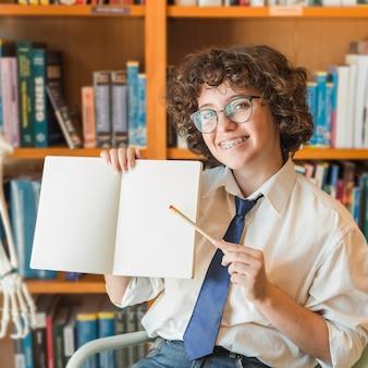 Adolescent joyeux pointant sur ordinateur portable vide