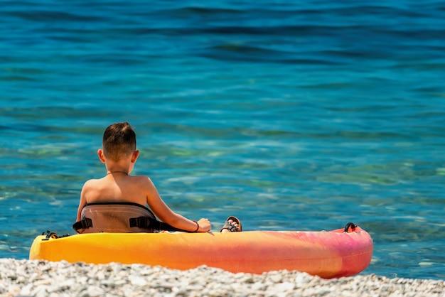 Adolescent sur un kayak sur la plage