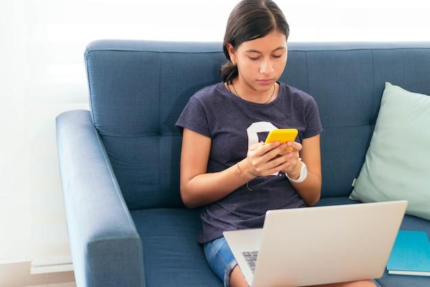 Adolescent latina sérieux regardant l'écran du téléphone, vérifiant ses e-mails, assis sur un canapé