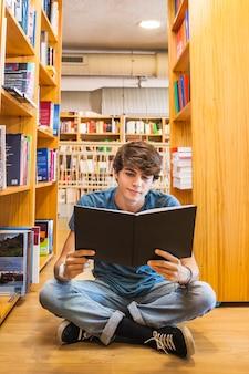 Adolescent, lecture sur le sol de la bibliothèque