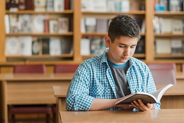 Adolescent, livre de lecture dans la bibliothèque