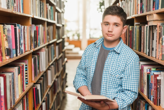 Adolescent avec livre ouvert en regardant la caméra