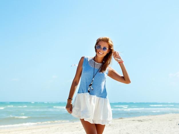 Adolescent avec des lunettes de soleil et robe bleue sur la plage
