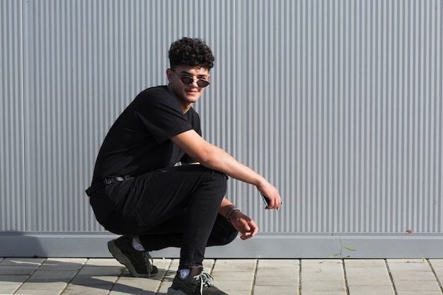 Adolescent mâle accroupi contre le mur gris