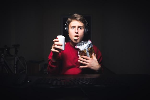 Adolescent mange une collation, regarde une vidéo effrayante sur ordinateur la nuit