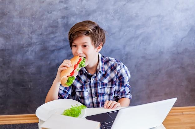 Adolescent mange un sandwich et surfe sur le web