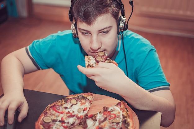 Adolescent, manger de la pizza assis à un ordinateur portable.