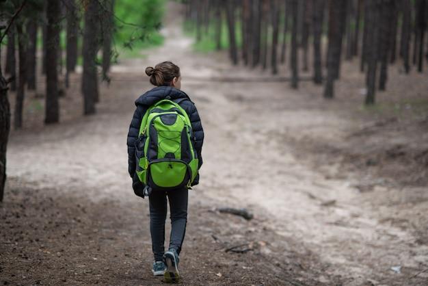 Adolescent marche seul à la forêt de printemps avec sac à dos. activité de style de vie pour les jeunes, le tourisme, les vacances.