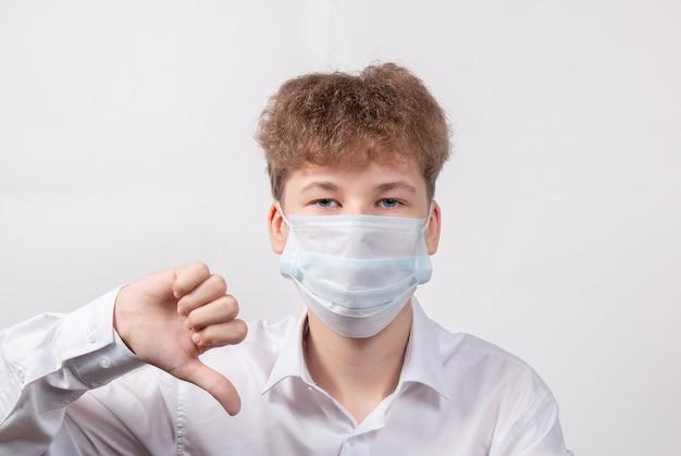 Adolescent en masque médical de protection sur un blanc